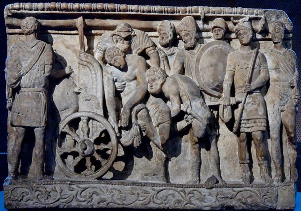 Menelaus and Meriones lifting Patroclus' corpse on a cart while Odysseus[on right] looks on. National Archaeological Museum Florence Wikipedia